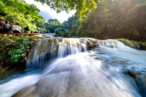 Long exposure of rapid waterfall with threshold flowing among tropical forest with green trees and people on bench admiring nature
