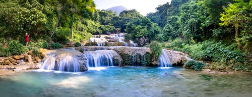 Wide angle of fast waterfalls streaming into calm river surrounded by green trees with lush vegetation and distant tourists in nature