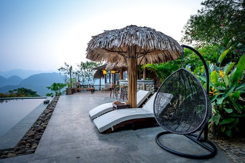 White loungers and thatched parasol with chair placed near swimming pool on terrace of tropical hotel with green exotic plants against mountain ridge on background