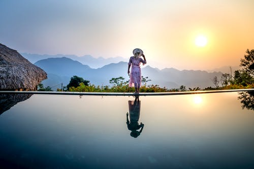 Back view of full body anonymous female in romantic dress and straw hat standing on poolside and looking away while enjoying sundown in amazing terrain