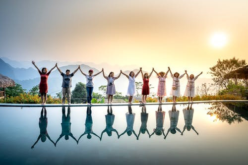 Happy full body ethnic people in summer clothes standing on poolside and holding hands with raised arms near calm water on sunset with amazing mountains on background
