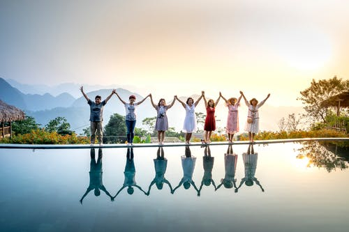 Group of happy people in colorful summer clothes raising hands and enjoying nature spending holidays together