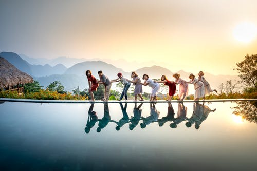 Group of happy people standing in chain above still water of lake and having fun in summer evening