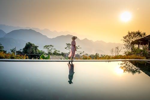 Woman walking along pool in evening