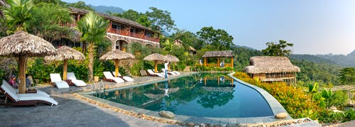 Big swimming pool outside hotel in tropics