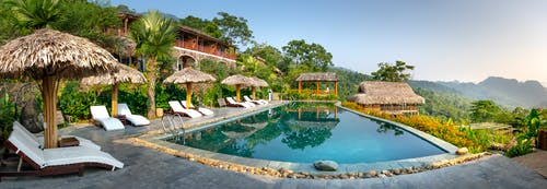 Exotic resort hotel with swimming pool with deckchairs and umbrellas located in calm tropical place