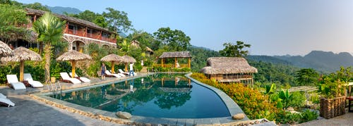 Small cozy hotel in south eastern style with swimming pool and deckchairs in tropical resort