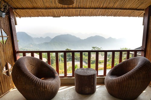 Comfortable armchairs and small side table on veranda near wooden barrier overlooking mountain ridge and green trees in tropical country