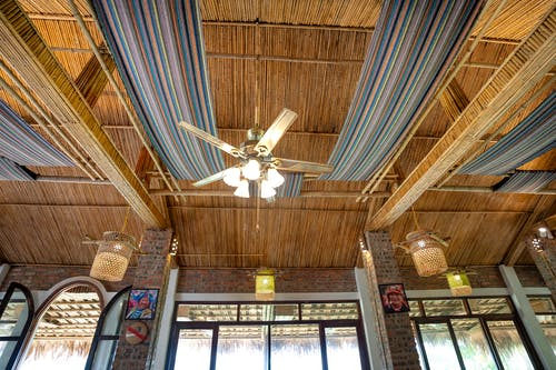 From below of glowing chandelier hanging on wooden roof with traditional colorful fabric near illuminated lamps in tropical cafeteria with windows