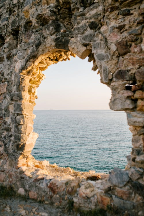 Natural window in rocky cave and blue ocean