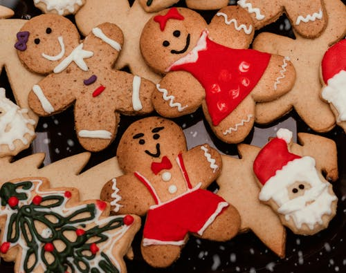 Top view stack of yummy gingerbread cookies in shapes of men Santa Claus head and Christmas tree scattered on table in kitchen