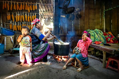 Side view of Asian woman in colorful outfit sitting with children and preparing food on bonfire in wooden rural barn in daytime