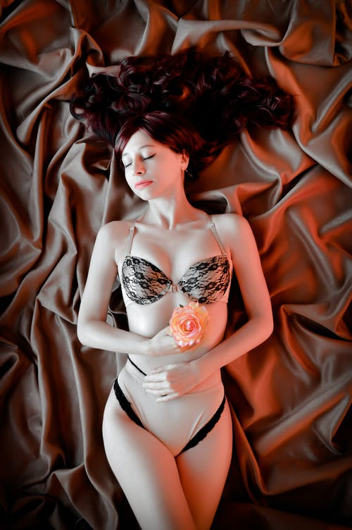 From above of sensual young slim lady in stylish underwear lying on draped silk bed sheet with closed eyes and flower in hand