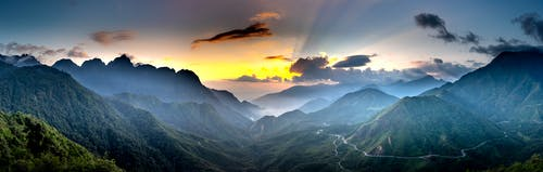 Panoramic view of majestic mounts with wavy roads under bright sky with fluffy clouds at sundown