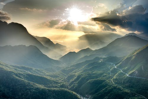 High ridges with wavy roadways illuminated by shiny sun