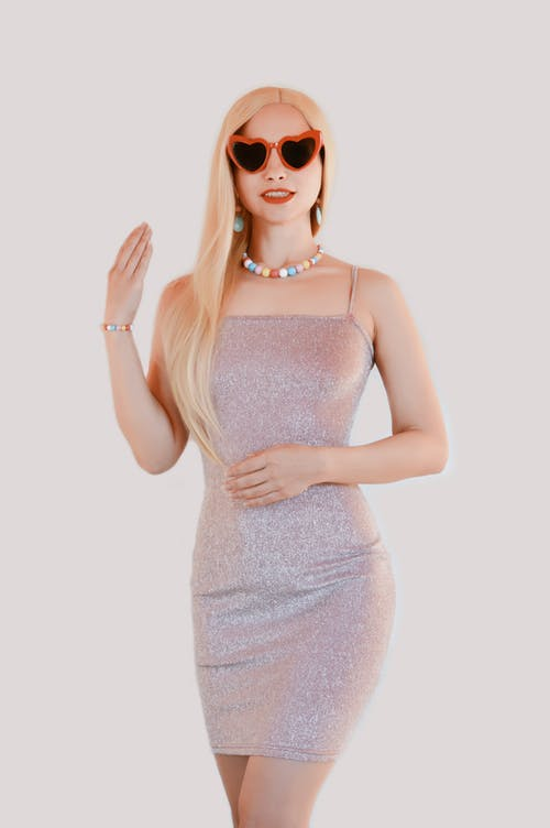Stylish young blondie in dress and sunglasses standing in white studio