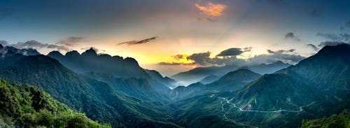 Magnificent mountains with wavy roads under cloudy sky at sunset