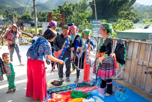 Ethnic vendor interacting with unrecognizable shopper in urban bazaar