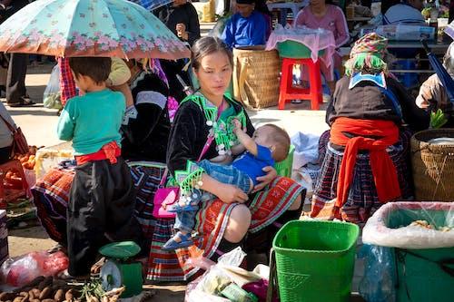 Ethnic vendor breastfeeding son against anonymous partner in market