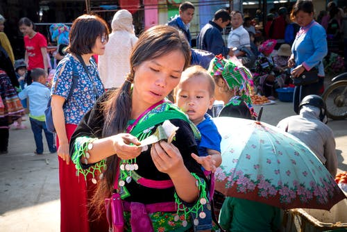 Young ethnic mom in traditional wear with baby and sticky rice in banana leaf in urban market