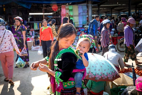 Young Asian mom with toddler child eating tasty sweet rice in banana leaf against anonymous shoppers in urban bazaar