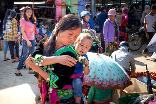 Asian mom carrying baby with sweet rice treat in market