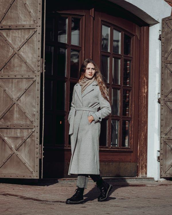 Woman in Gray Coat Standing in Front of Brown Wooden Door