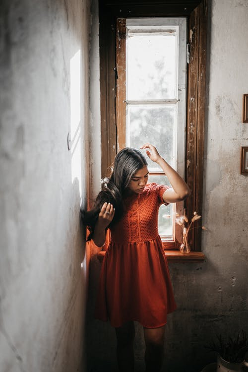 Ethnic woman touching hair in old house