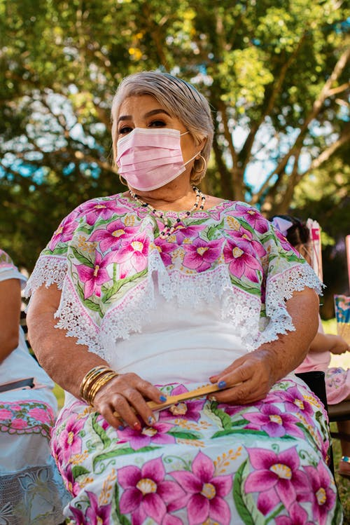 Woman in White and Pink Floral Dress Wearing White Face Mask
