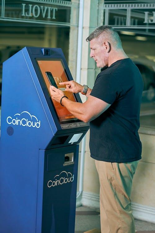 Man in Black Crew Neck T-shirt using an ATM