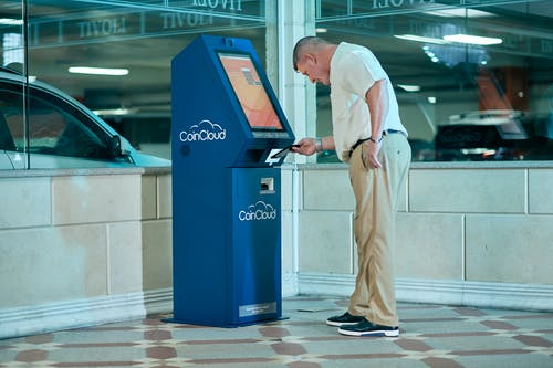 Man in White Dress Shirt and Brown Pants Standing Near Blue and Black Atm Machine