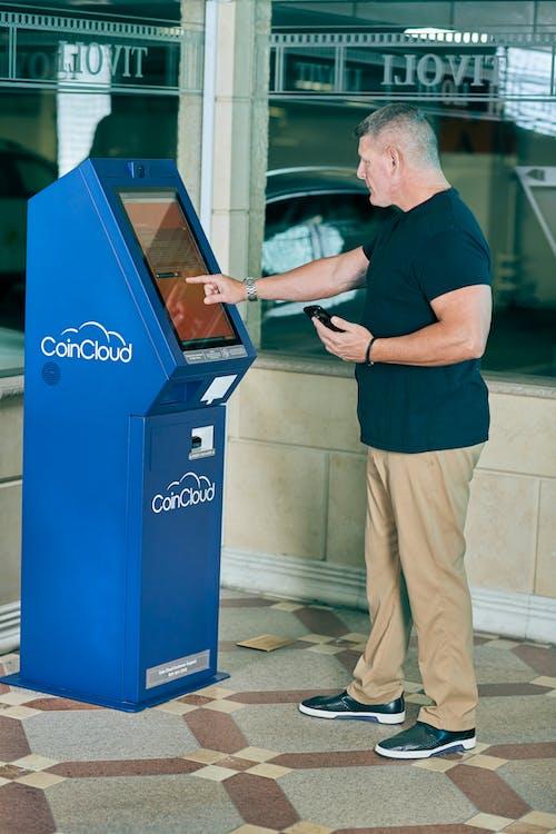 Man in Blue Crew Neck T-shirt using an ATM