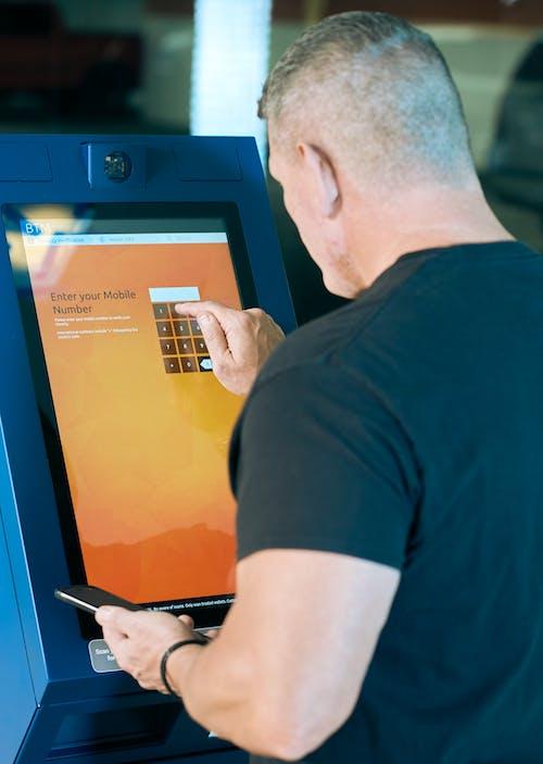 Man in Black Crew Neck Shirt using ATM