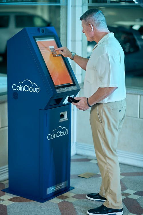 Man in White Dress Shirt and Beige Pants Standing Beside Pepsi Vending Machine