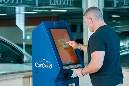 A Man in Black Shirt Using ATM
