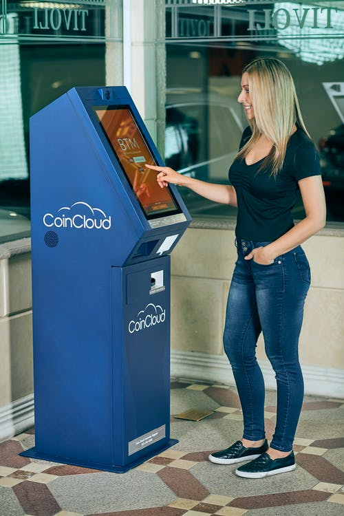 A Blonde-Haired Woman in Black Top Using ATM