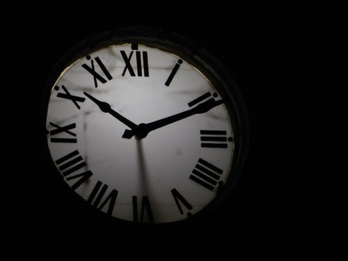 Round mechanical clock with black arrows and numbers on white face ticking on black background in darkness