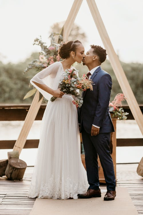 Diverse newlywed couple kissing on wooden terrace