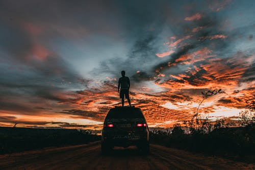 Silhouette of Man Standing on Car