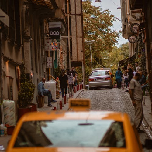 Narrow urban street with cars and people