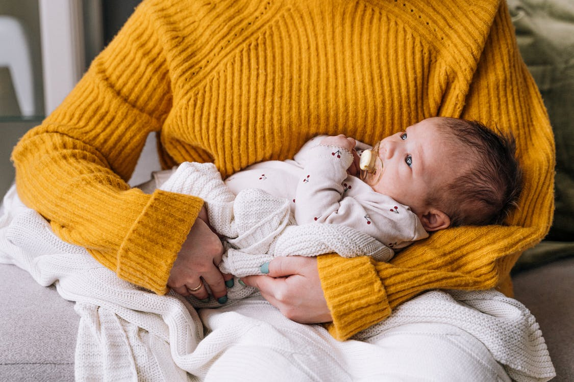 Baby in White Shirt Lying on Yellow Knit Textile