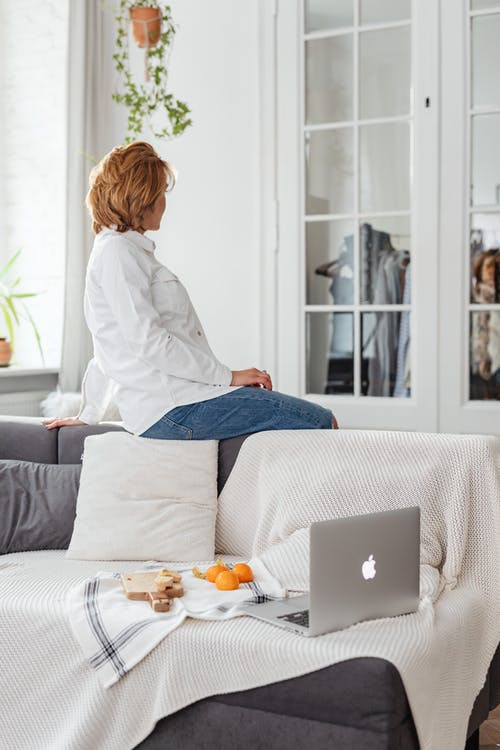 Woman in White Shirt Sitting on Gray Couch