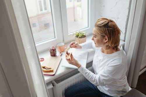 Woman Spreading Jam on Bread