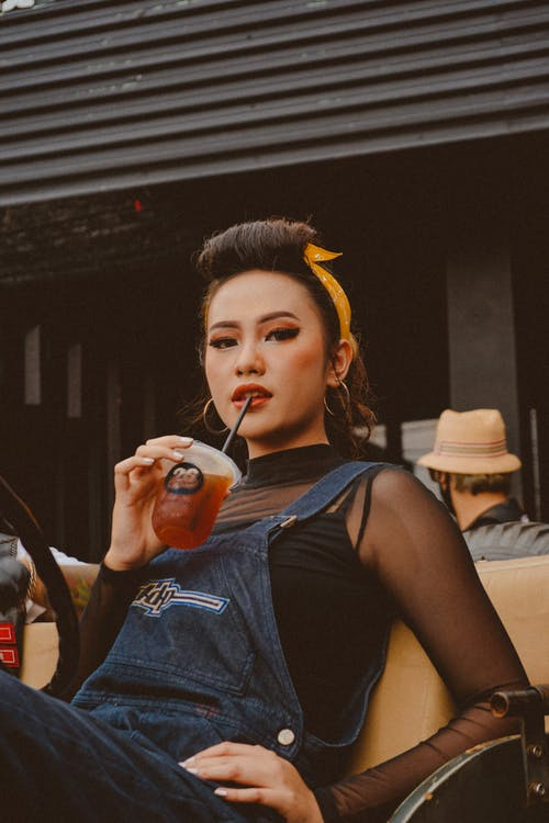 Millennial ethnic woman enjoying delicious drink on transport in town