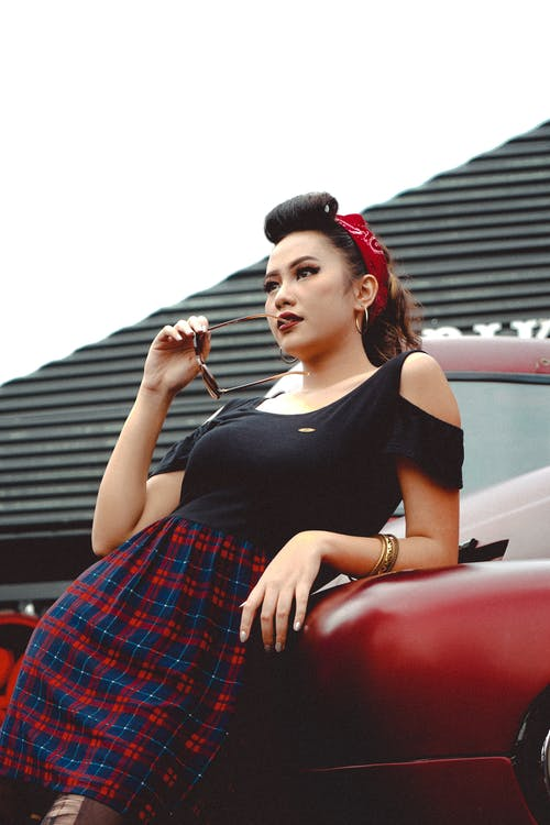 Stylish ethnic model leaning on vehicle in town