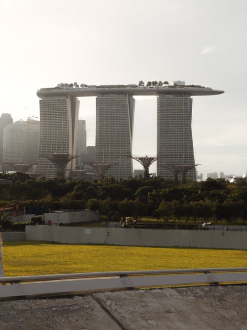 Exterior of famous creative Marina Bay Sands hotel located near lush Botanic Gardens on clear sunny day in Singapore