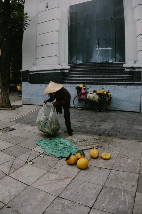 Faceless Asian male fruits seller wearing typical conical hat collecting fruits into plastic bag after working on city street