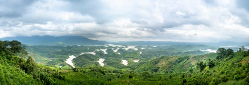 Panorama of curvy river flowing among green terrain in hilly terrain covered with grass against mountain ridge and cloudy sky