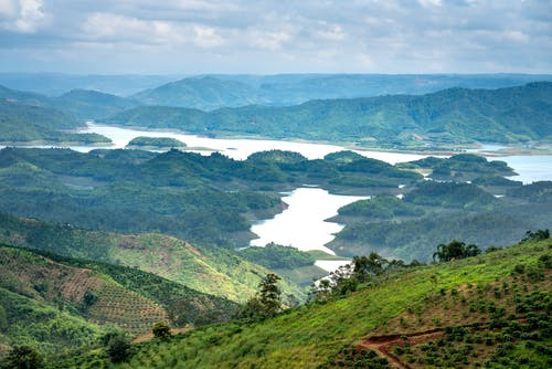 Calm river flowing among green hills covered with grass and agricultural fields against cloudy sky and mountain ridge in nature