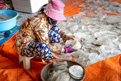 Side view of anonymous ethnic female in panama hat preparing rice sheets with chia seeds on textile